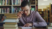 учебник : Young handsome teenage man wearing glasses sitting at table in university library thinking over calculations in copybook. He is looking away and witing thoughtfuly Стоковые видеозаписи