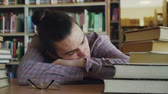 akademický : Handsome young teenage man sitting with his head on table is sleeping in school library surrounded by huge piles of books. His glasses are lieing in front of him