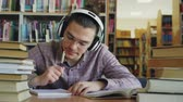 выше : Young caucasian male student with big headphones is sitting at table in library. Many books are aroung him, he is smiling listening to music and writing Стоковые видеозаписи