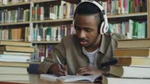 prateleira de livros : Handsome african american male student wearing headphones is listening to music sitting at table in big spacious library writing lecture surrounded by books Vídeos