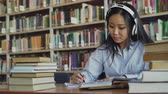 mosolyogva : Pretty positive asian teenage student with headphones on head listening to music is sitting at table in big library holding book and writing down summary