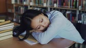 montão : Young beautiful tired asian female student is sitting at desk with her head on it, she is sleeping on textbook surrounded by piles in big university library