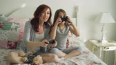 closeness : Funny laughing girl with happy young mother have fun while playing computer console games on TV sitting on bed at home in the morning in cozy bedroom. Daughter embracing mom after winning