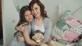 closeness : Portrait of adorable smiling girl embracing her happy mother and looking at camera together while sitting on bed in bright bedroom at home
