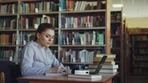 выше : Beautiful serious caucasian female student sitting at table with books in library writing down summary in copybook using laptop computer