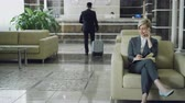 bagagem : Attractive businesswoman sitting in armchair talking mobile phone with notepad while businessman with luggage walking through hotel lobby to reception desk