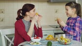doba jídla : Happy family of young mother and cute daughter have fun grimacing silly with vegetables while cooking in the kitchen at home Dostupné videozáznamy
