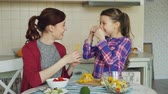 doba jídla : Joyful mother and cute cheerful daughter have fun grimacing silly with vegetables while cooking in the kitchen at home. Family, cook, and people concept