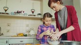 celebração : Happy mother and cute daughter cooking together and having fun stirring dough in hands. Family, food, home and people concept