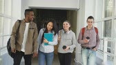 spacious : Multi-ethnic group of students walking down white spacious university corridor and talking happily after passing exams. Education, people and friendship concept