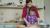 padaria : Happy mother teaching her little cute daughter rolling dough while cooking together in the kitchen at home on holidays. Family, food and people concept Stock Footage