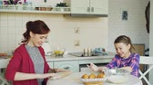 штифт : Young mother and cute daughter cooking together talking in the kitchen on weekend. Little girl clapping hands with flour and laughing. Family, food, home and people concept
