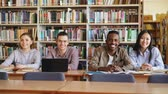 campus : Portrait of four multi-ethnic students sitting at long desk in big spacious library with piles of books looking at camera and smiling positively
