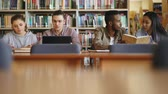 ders kitabı : Multi-ethnic group of students siting in library with books and laptop on table getting ready for examination together smiling and laughing Stok Video