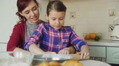 штифт : Cheerful mother talking to cute daughter mixing and rolling dough while cooking in the kitchen on weekend. Family, food, home and people concept