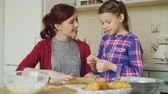 штифт : Cheerful mother cooking in the kitchen while cute daughter coming and embracing mom in the morning. Family, food, home and people concept