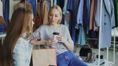 entreter : Young woman sitting in clothes shop, holding coffee and talking to her female friend. Ladies having rest after going shopping.