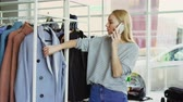 cabide : Cute blond girl is chatting on smart phone in boutique, touching clothes on hangers and smiling. Lots of fashionable clothes and large window in background. Stock Footage