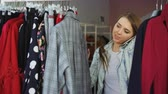 wieszak : Close-up shot of pretty cheerful girl choosing clothes in boutique talking on mobile phone. She is going through fashionable jackets and skirts, looking at them and touching them with pleasure