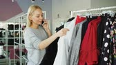 cabide : Female customer is slowly going through fashionable clothes on hanger in spacious shop. Other customers are moving around with clothes and shoes in the background. Stock Footage