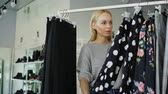 cabelos longos : Pretty blond girl is choosing clothes in boutique. She is looking through fine garments and taking dress from the rails, examining its quality and length.