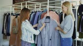 продавщица : Shop assistant is helping young woman, bringing her coat and telling about model. Customer is touching it, comparing with other clothing while chatting with saleswoman Стоковые видеозаписи