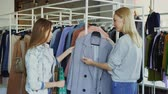 butik : Young woman is helping her friend to find coat. She is bringing her new model, telling about it and showing its advantages. Girls are talking and smiling.