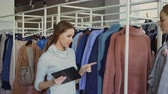 dando : Young businesswoman is using tablet while checking goods in her clothing store. Assistant is coming with garment and asking advice. Business owner is giving orders. Stock Footage
