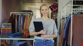 departamento : Portrait of successful young businesswoman standing in her clothing store, holding tablet, smiling and looking at camera. Spacious boutique with womens garments in background.