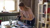 table styling : Young attractive female blogger using digital camera to shoot colourful pictures from travel displayed on table. She is moving photos and making collages. Stock Footage