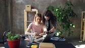 иллюстрировать : Young designer is drawing images in notebook sitting at table while female photographer is coming to her with camera. Women start discussing project and watching photos on screen.