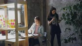frasco pequeno : Female friends and business partners are working together in modern office. Blonde is sitting at table and collecting pictures, brunette is watering plants.