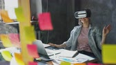 hitech : Attractive young woman is sitting at table and wearing virtual reality glasses. She is moving hands and and having VR experience in modern lof office