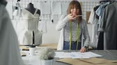 rascunho : Ambitious creative female tailor is placing garment sketches on studio desk and shooting them with smartphone. Presenting drawings of new collection concept.