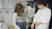 measure : Pretty customer is trying on tailored shirt and sharing her opinion while clothing designer is measuring and checking garment and taking to client in light studio.