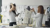inç : Professional seamstress is measuring patterns on mannequin with measure-tape while her coworker is working with tablet to write down measurement data. Stok Video