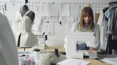 dikiş : Self-employed clothing designer is working with sewing machine, stitching textile and looking at sketches lying on studio table. Everyday work at tailors shop concept.