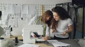 сшивание : Young woman is working with sewing machine and checking stitches when her colleague is coming to her with sketch. Women are looking at fabric and talking.