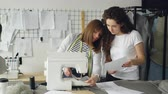 dikiş : Attractive dressmakers are looking at sketches and working with sewing machine, then checking stitches and adjusting equipment. Professional teamwork concept.