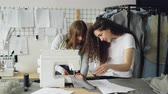 craft : Professional seamstress is stitching fabric with sewing machine then adjustig equipment while her female colleague is showing her sketches. Studio with tailoring items in background.