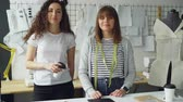 colega de trabalho : Portrait of two female clothing designers entrepreneurs standing in workshop together and looking at camera. One woman is holding take-out coffee, other is touching studio desk.