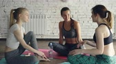 instrutor : Pretty yoga students are talking with instructor sitting on mats after practice, chatting and laughing emotionally. Friendly relations in wellness center concept.