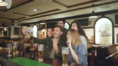 память : Group of friends are taking selfie via smartphone in nice pub. Beautiful people in casual clothes are posing and having fun. Friendly relaxing atmosphere, happiness concept. Стоковые видеозаписи