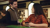 atender : Attractive brunette is checking smartphone at bar counter when young man is getting acquainted with her. Young people are chatting, smiling and clinking glasses. Stock Footage