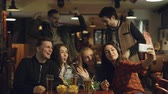 память : Happy young people in casual clothes are taking selfie in bar. They are posing, making silly faces, laughing and gesturing. Funny photos for good memories concept. Стоковые видеозаписи