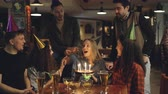 aplauso : Young blonde is making wish and blowing out burning candles on birthday cake while having party in cafe with friends. Happy people are laughing and clapping hands. Vídeos