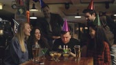 aplauso : Best friends are congratulating young man on birthday, he is blowing out candles on cake and thanking his mates for great party. Funny holiday with friends concept.