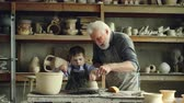 molde : Cute boy is molding clay on throwing wheel while his caring grandfather is teaching and helping him, giving advices. Shelves with numerous ceramic pots in background.