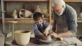 forming : Curious boy is learning pottery from his experienced grandfather in small home studio. Child is forming clay to make pot on potters wheel, his granddad is helping him.
