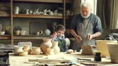 vnuk : Cheerful little boy is throwing pieces of clay on work table while helping his grandfather in potters workshop. Happy childhood, family traditions and hobby concept.